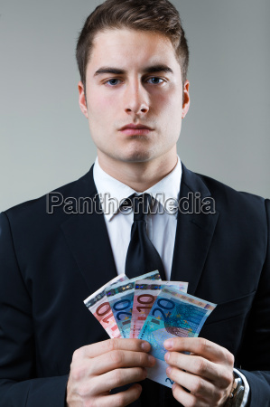 young man in formalwear holding money