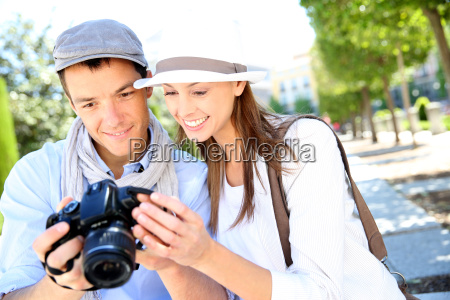 cheerful couple with photo camera in