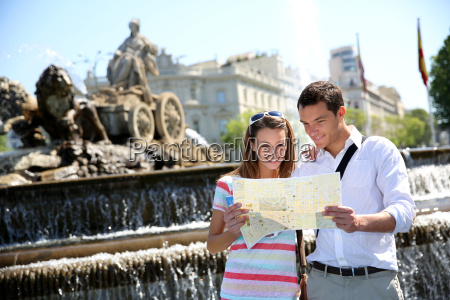 couple of tourists reading map in