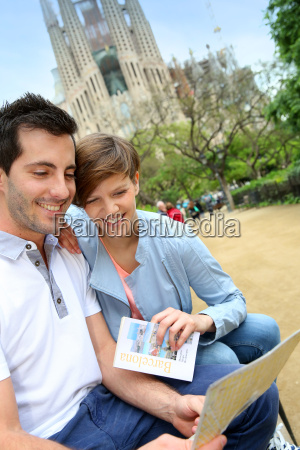 couple reading travel guide by the