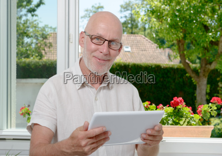 mature man at home websurfing on