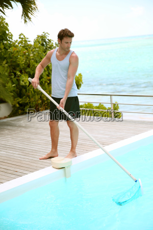 swimming pool service man cleaning water