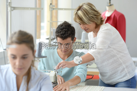 teacher helping student with sewing machine