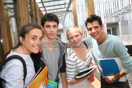 cheerful students standing outside school building