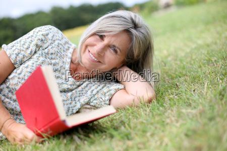 senior woman reading book laid on