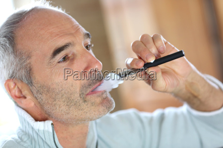 portrait of senior smoker with electronic