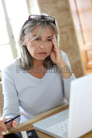 perplexed senior woman in front of