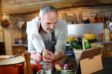 mature man in kitchen reading recipe