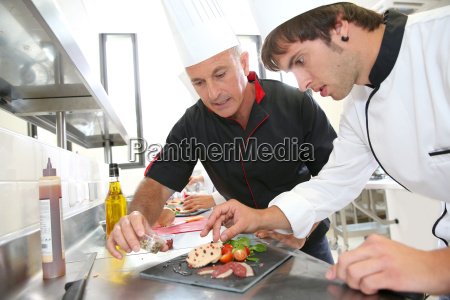 chef helping student in catering to