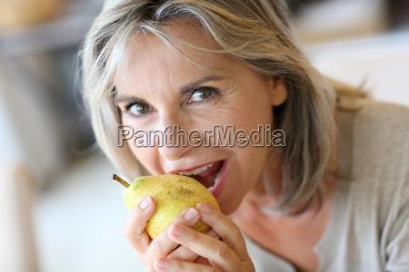 portrait of senior woman eating pear