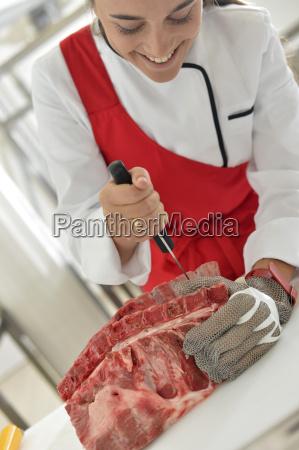 butcher girl at work cutting ribs