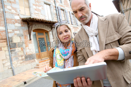 senior couple visiting city with map