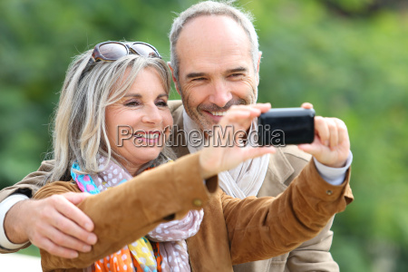 cheerful senior couple taking picture with