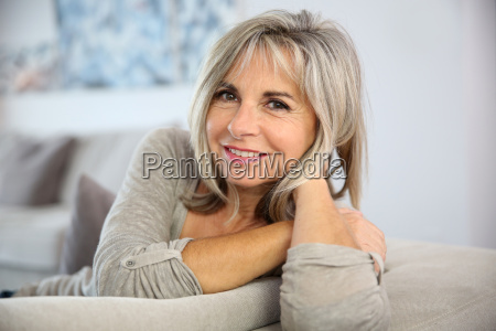 smiling senior woman sitting in couch