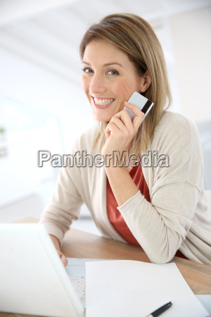 cheerful middle aged woman buying on