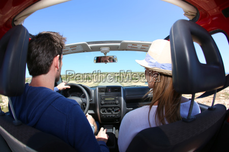 back view of couple driving convertible