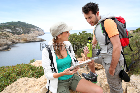 couple of hikers reading map and