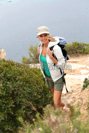 young woman hiking by the sea