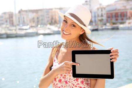 beautiful tourist girl showing tablet screen