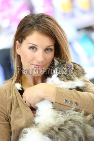 portrait of smiling woman holding cat