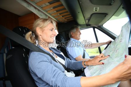 senior couple riding camper and reading