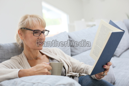 senior woman reading book and relaxing