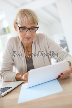 senior woman filling form online with
