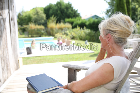 senior woman reading book by swimming