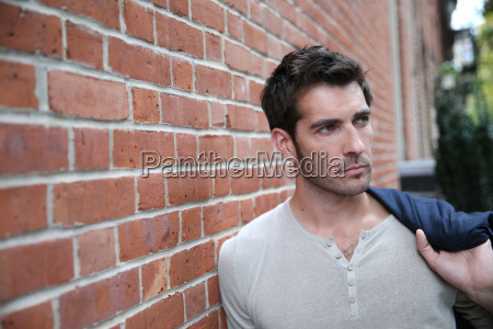 man leaning on wall in the