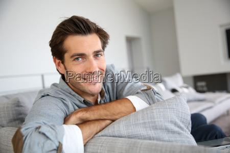 single man relaxing in sofa at