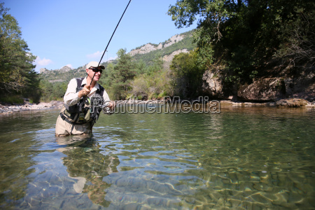closeup of fisherman fly fishing in