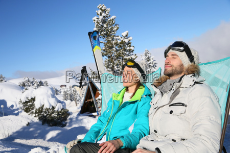 couple of skiers sunbathing in long