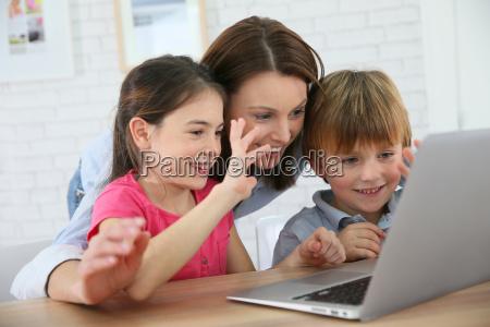 family of three using laptop video