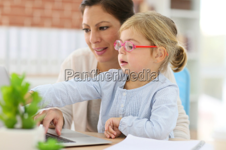 mother working at home office with