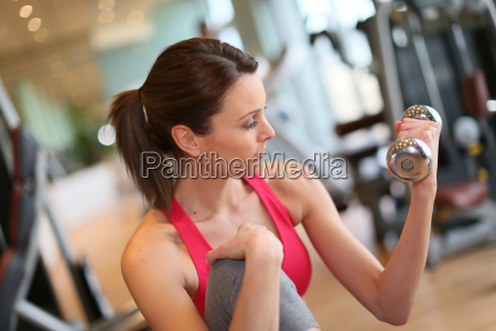 cheerful athletic woman lifting dumbbells in