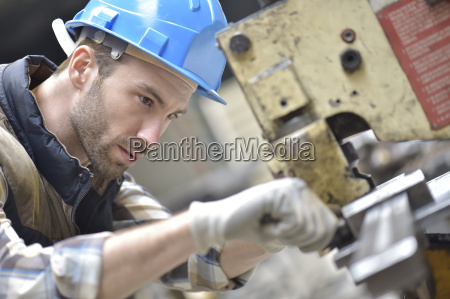 industrial worker working on machine in