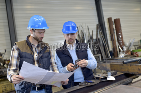 engineer with mechanical worker checking on
