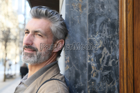 mature man leaning on building wall