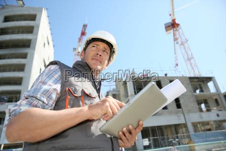 entrepreneur on building site using tablet