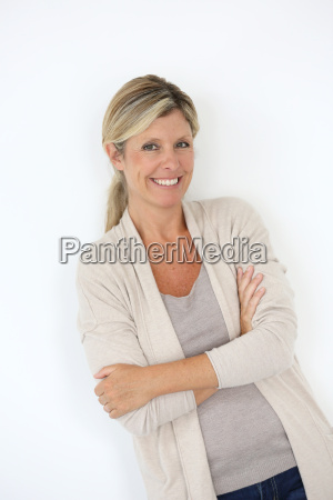 mature blond woman standing on white