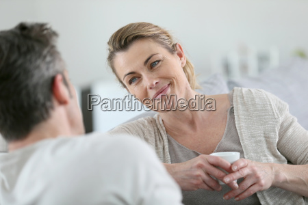 mature couple talking together in sofa