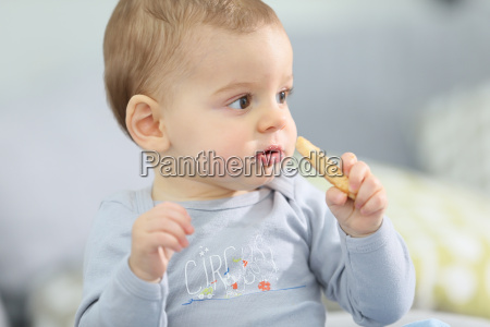 portrait of cute baby boy eating