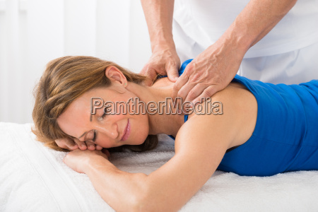 person giving massage to woman