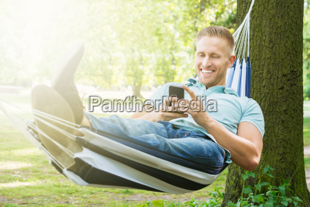 man lying in hammock using mobile