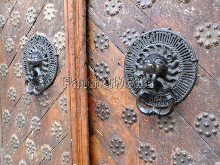 iron lion knockers on a wooden