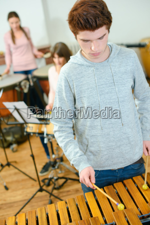 teenager learning to plat the xylophone