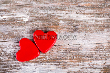 two red hearts on wood background