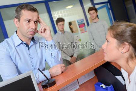 man at reception desk looking worried