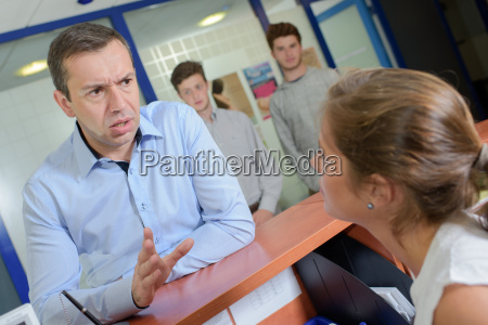 man at reception desk getting angry