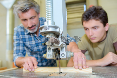 carpenter teaching apprentice to use a
